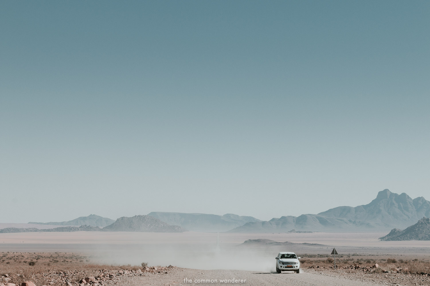 A car driving along a long dirt road in Namibia