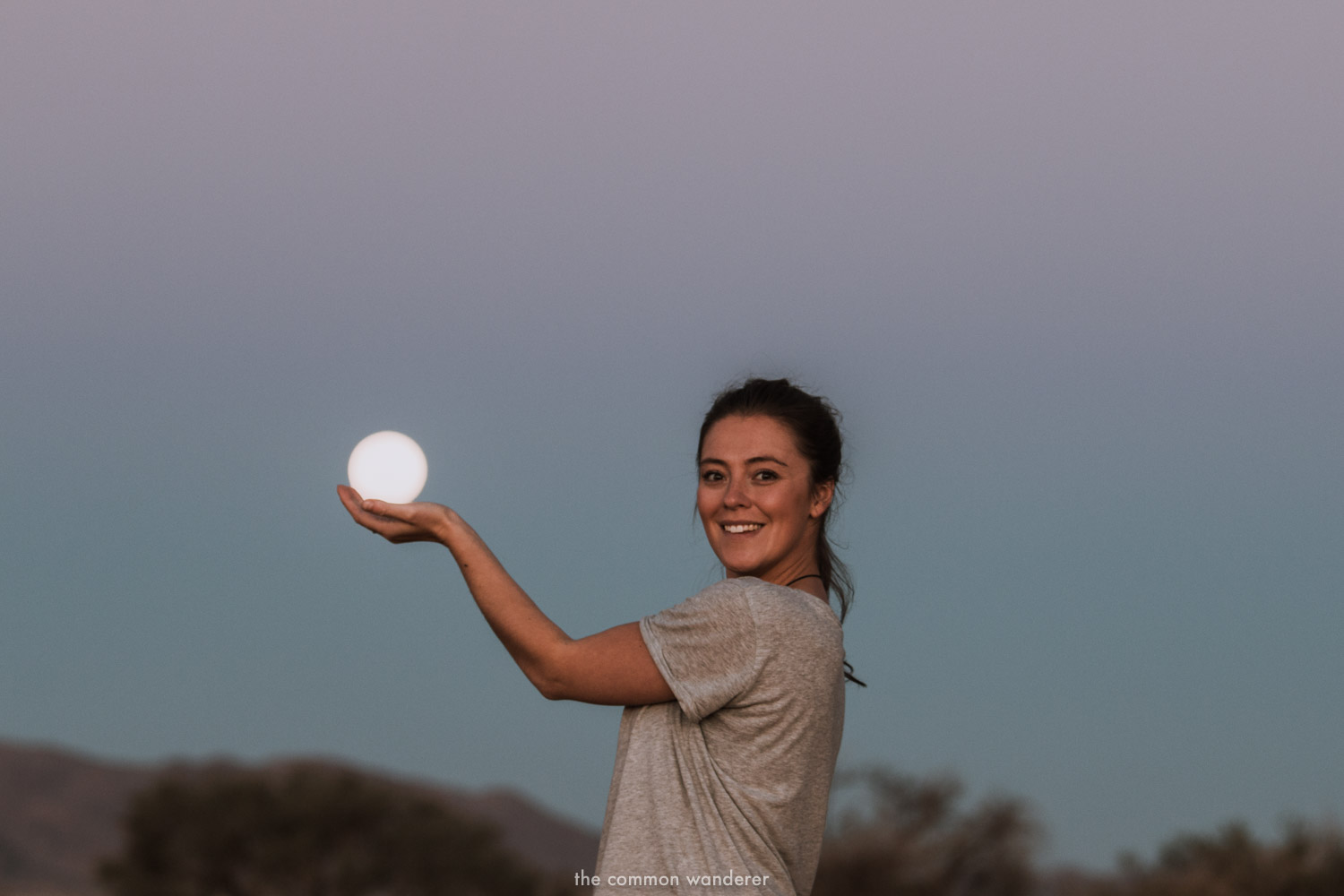 A woman cups a full moon in Namibia