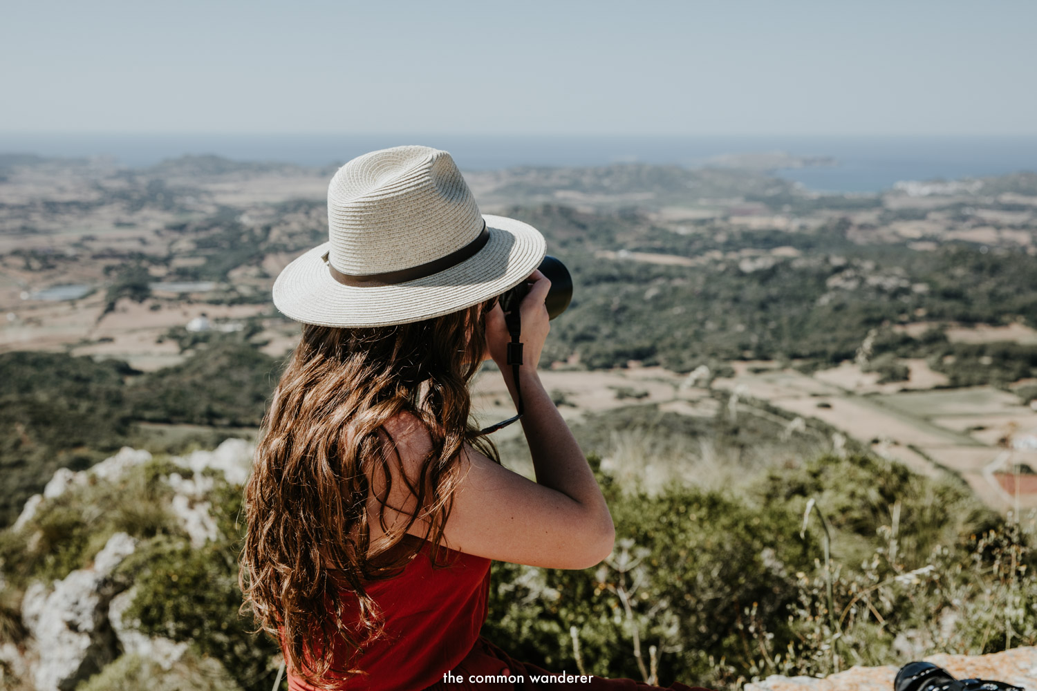 A woman takes a photo over Menorca from Monte Toro, Spain