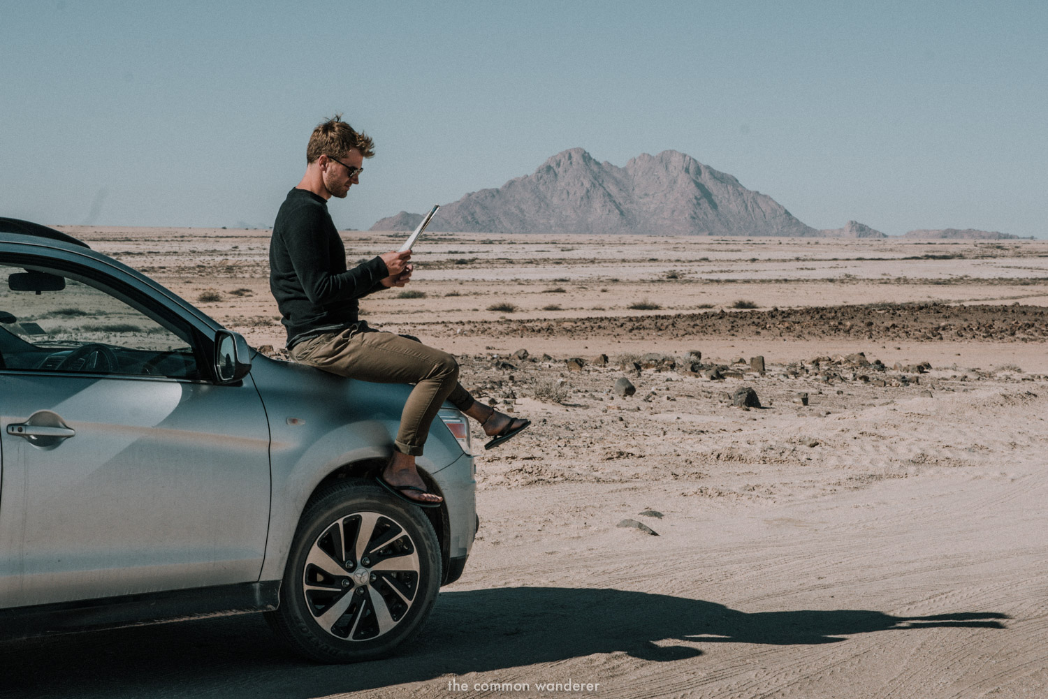 A man reads a map with Spitzkoppe mountain range in the background, Namibia road trip itinerary