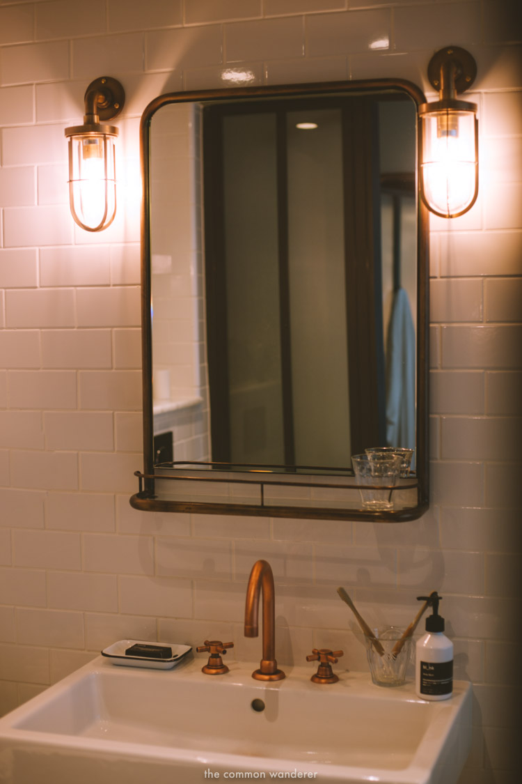 Copper finishings, subway tiles and vintage lamps in the bathrooms of the Hoxton. - THECOMMONWANDERER.COM