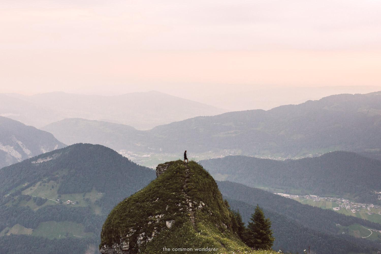 A man stands overlooking Bregenzerwald on a hike to Kanisfluh