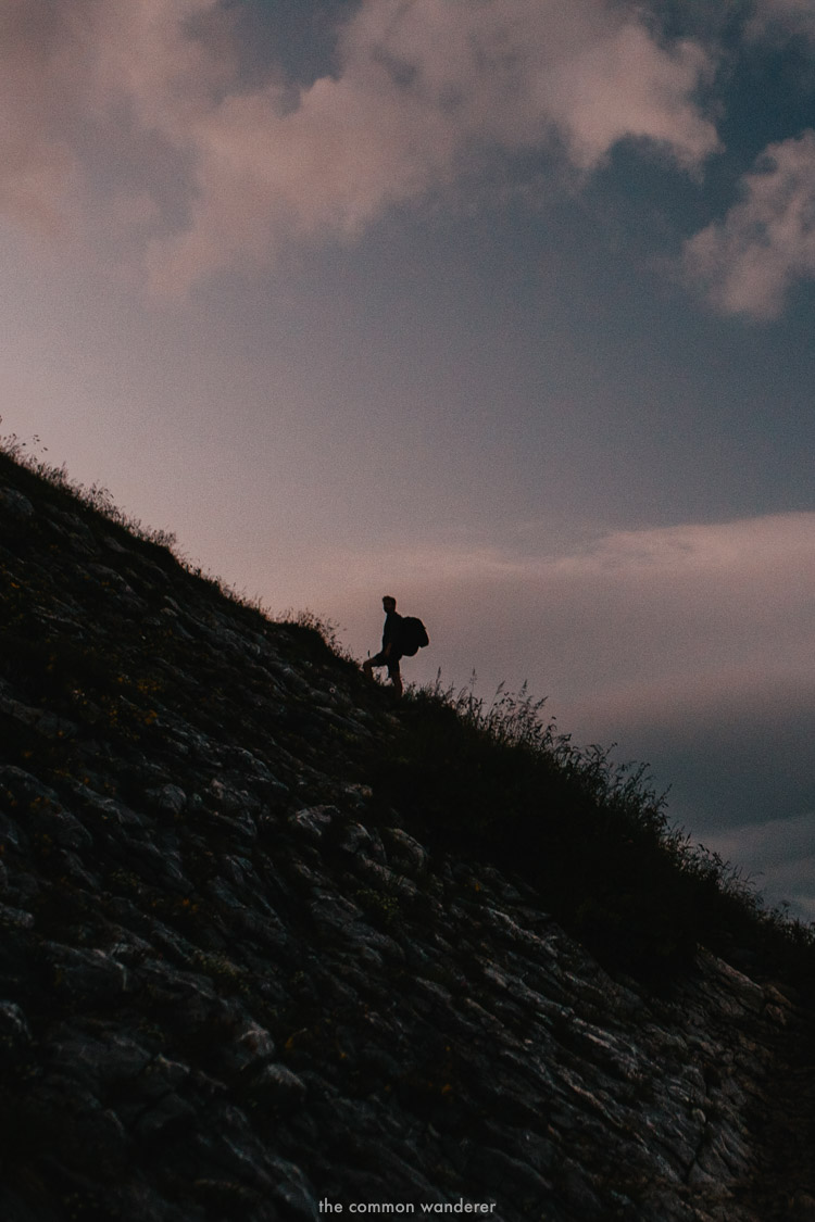 A man is silhouetted by the rising sun on the way up to Kanisfluh mountain, Vorarlberg