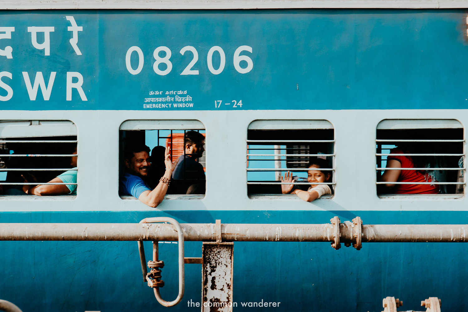 A family smile out the window of a train in India