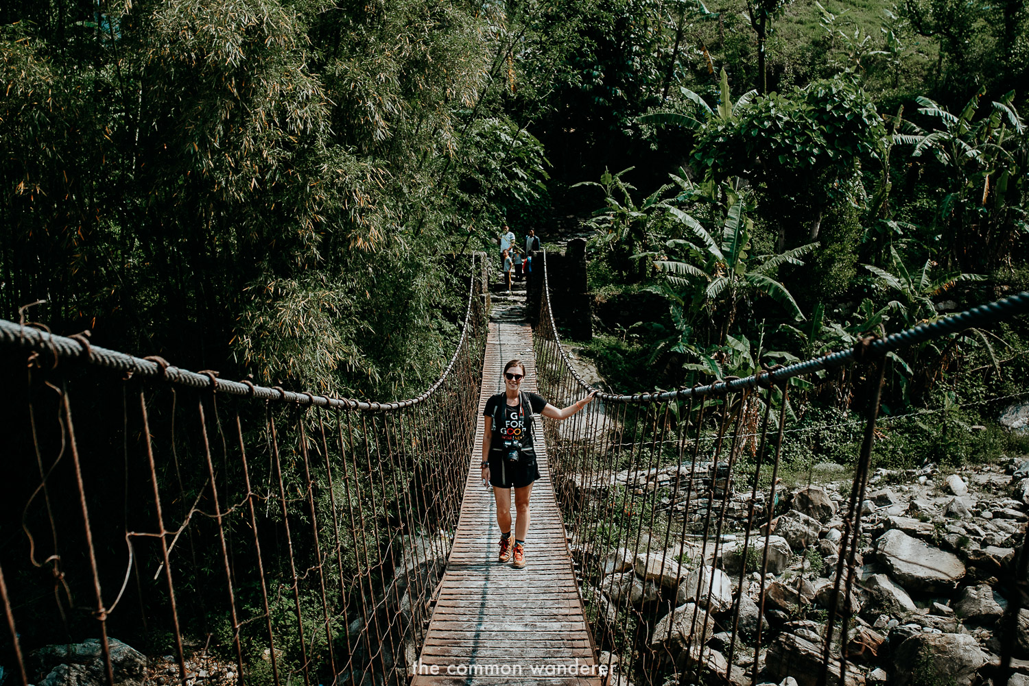Walking across a suspension bridge to start the Poon Hill trek, Nepal