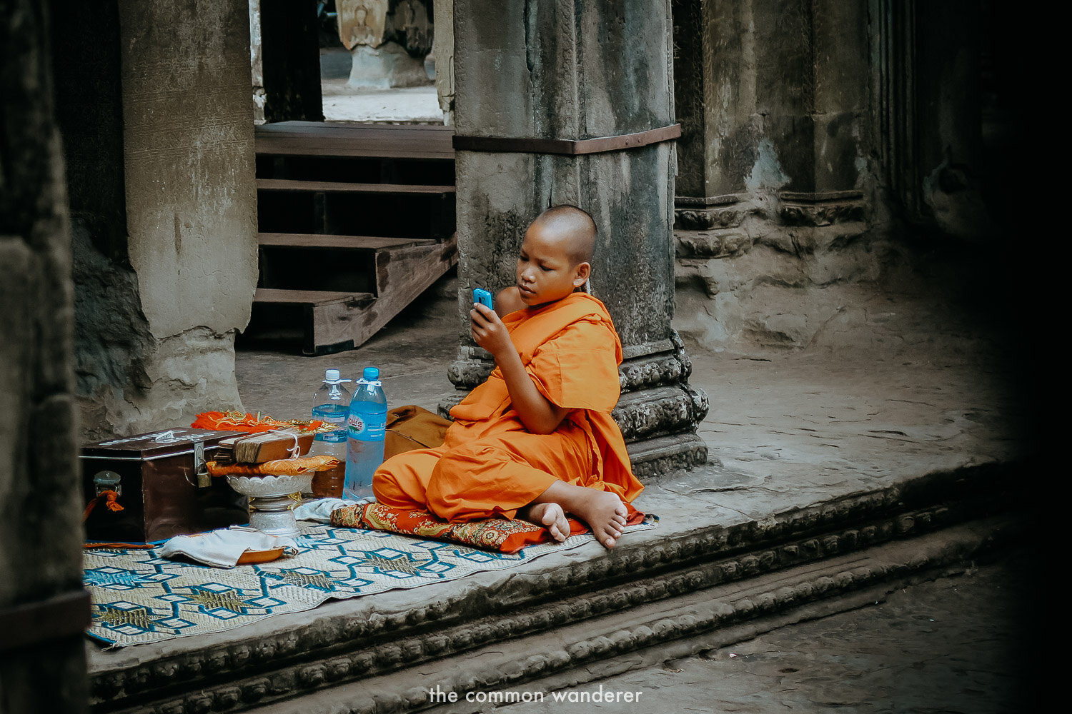 A monk on his phone in Angkor Wat, Cambodia