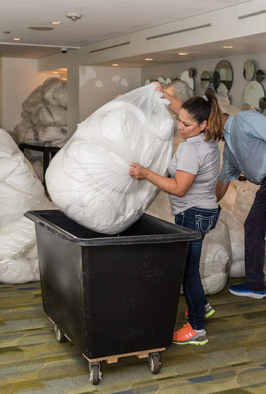 Volunteers collect thousands of bed linens from the Pier Sixty-Six Hotel for donation to various Broward County homeless aid organizations