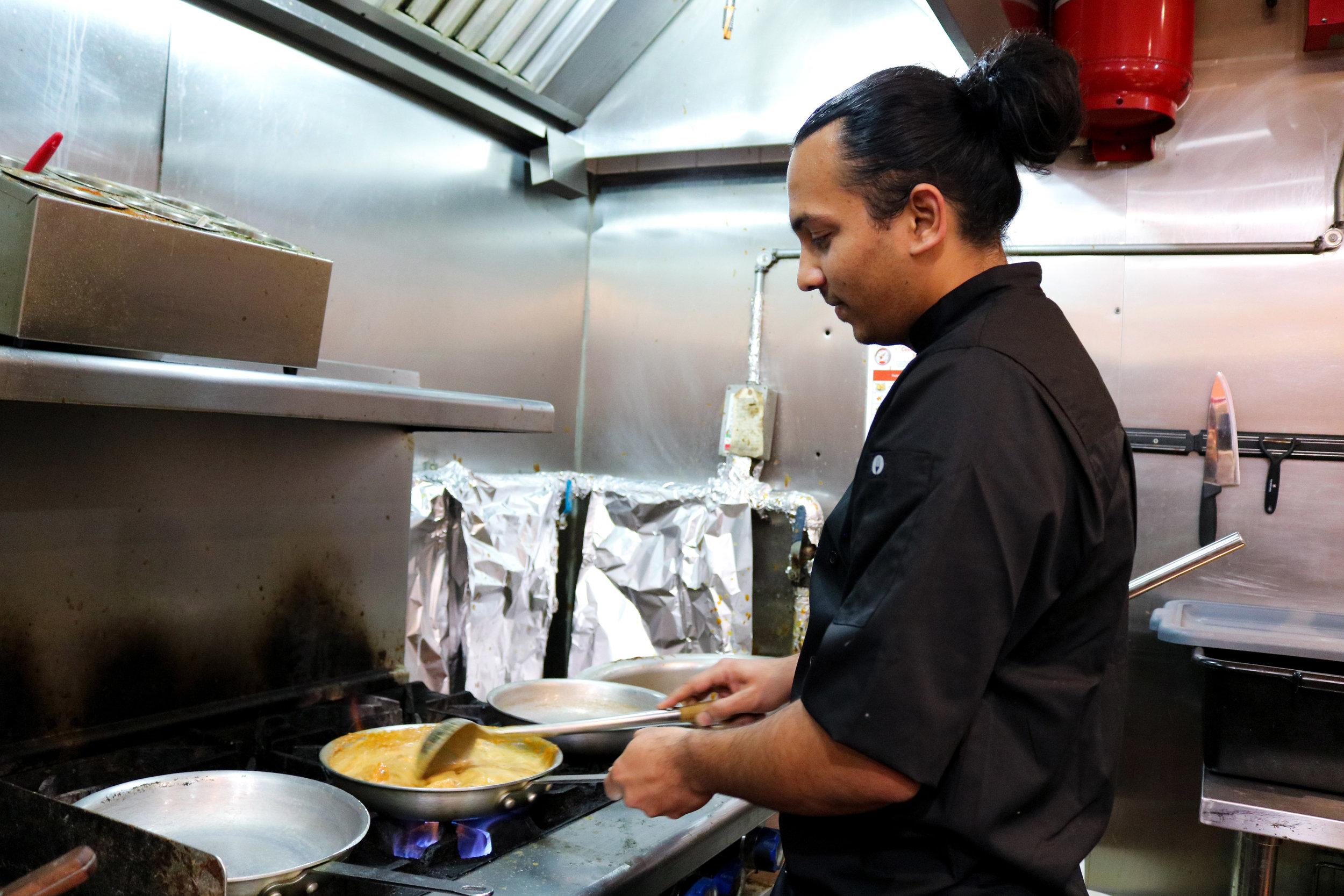 Bombay Roti Owner Gopi cooking butter chicken.jpg