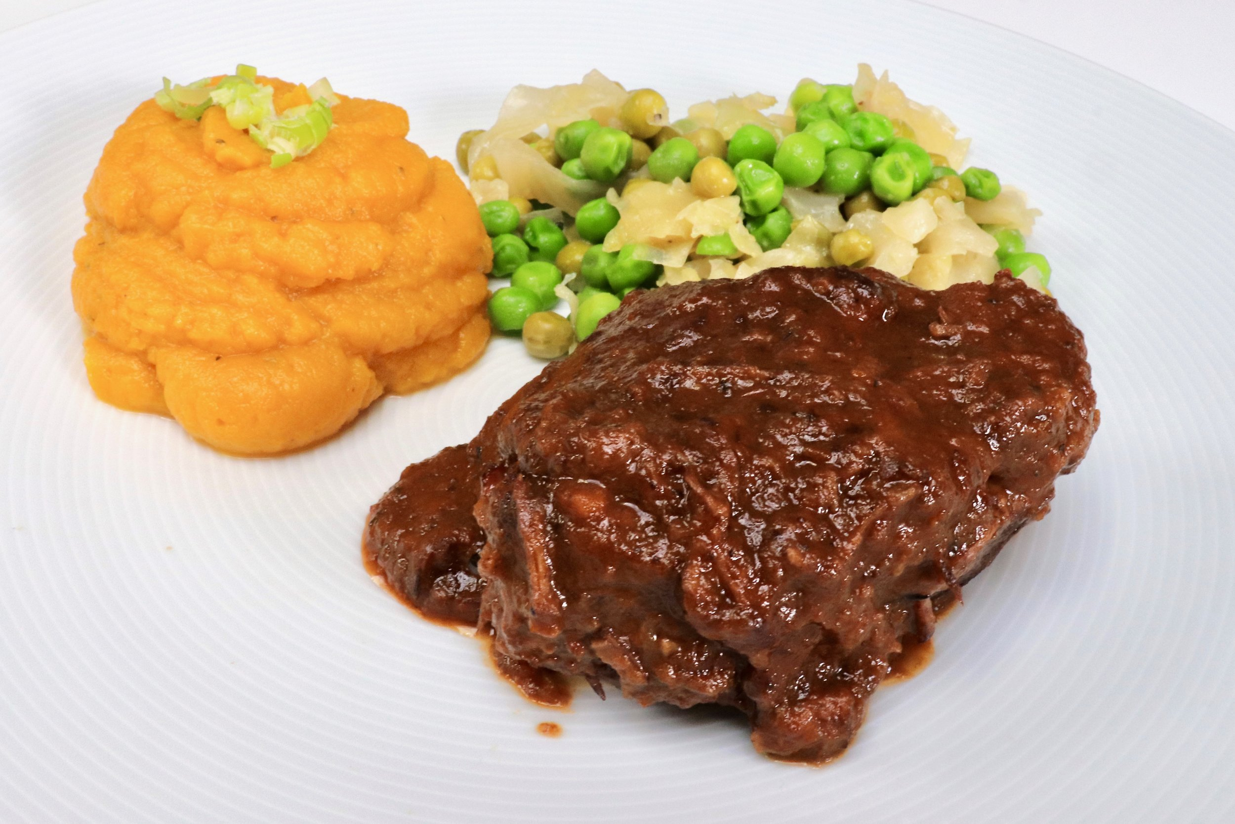 Feather blade of beef with chilli pumpkin purée and buttered cabbage and peas