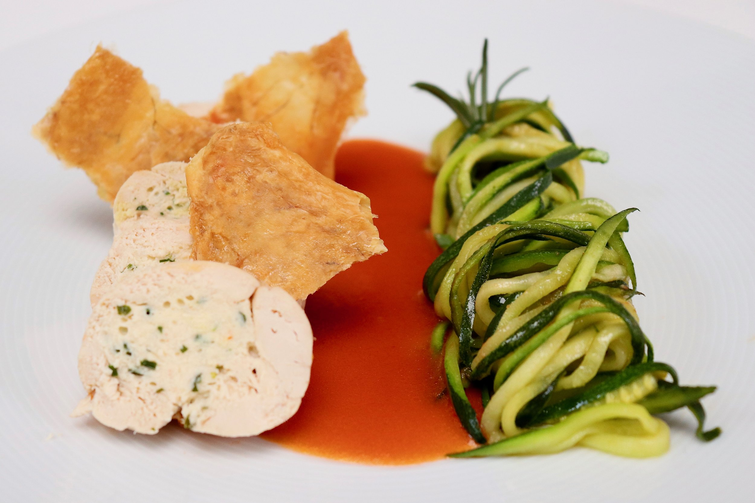 Stuffed supreme of chicken with crispy chicken skin, courgette spaghetti and tomato butter sauce