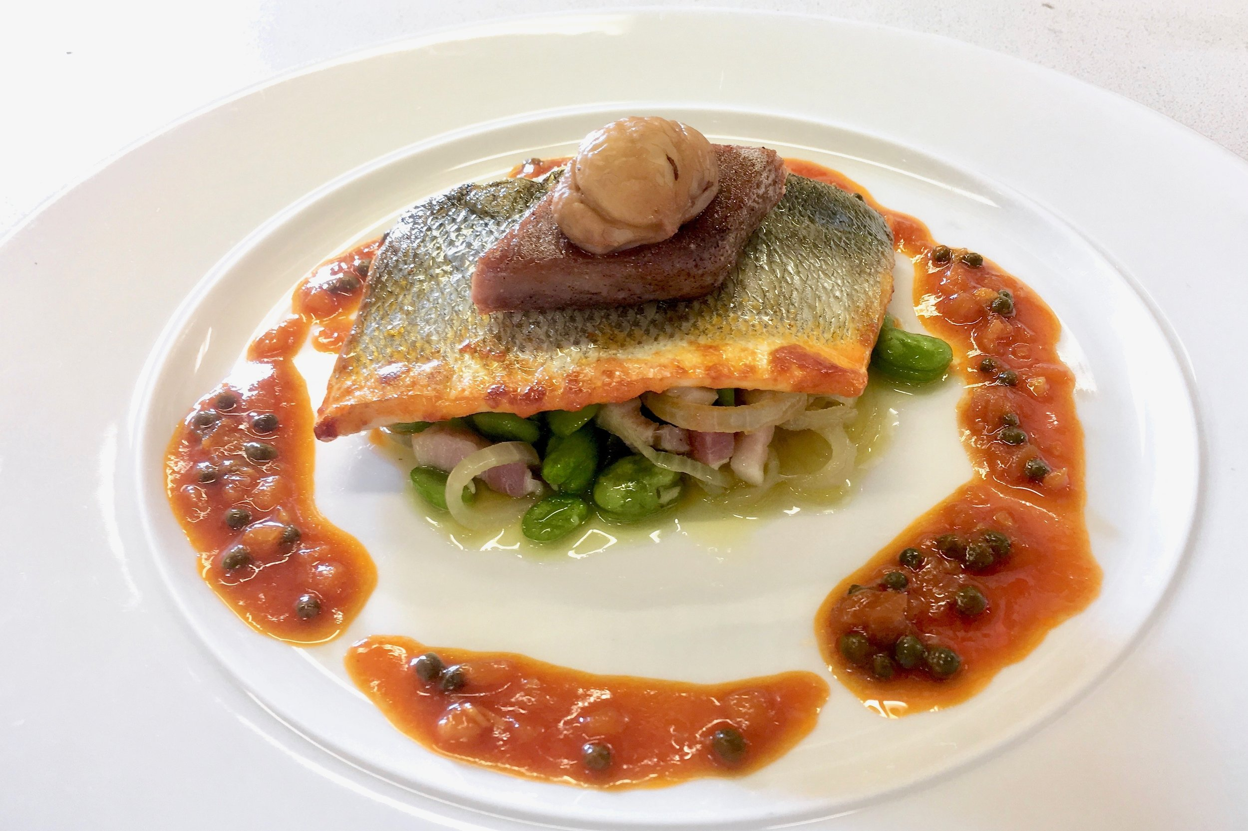 Baked sea bass from Bastia with broad beans and pancetta ragoût