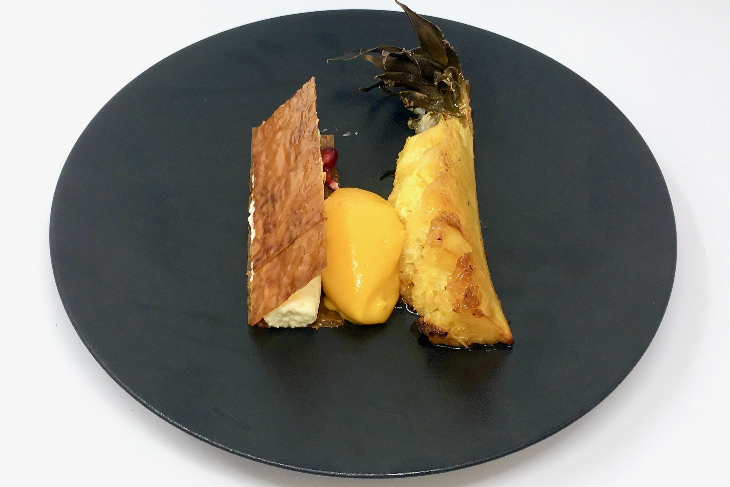 Caramelised pineapple with coconut and white chocolate mousse, mango sorbet, and pomegranate