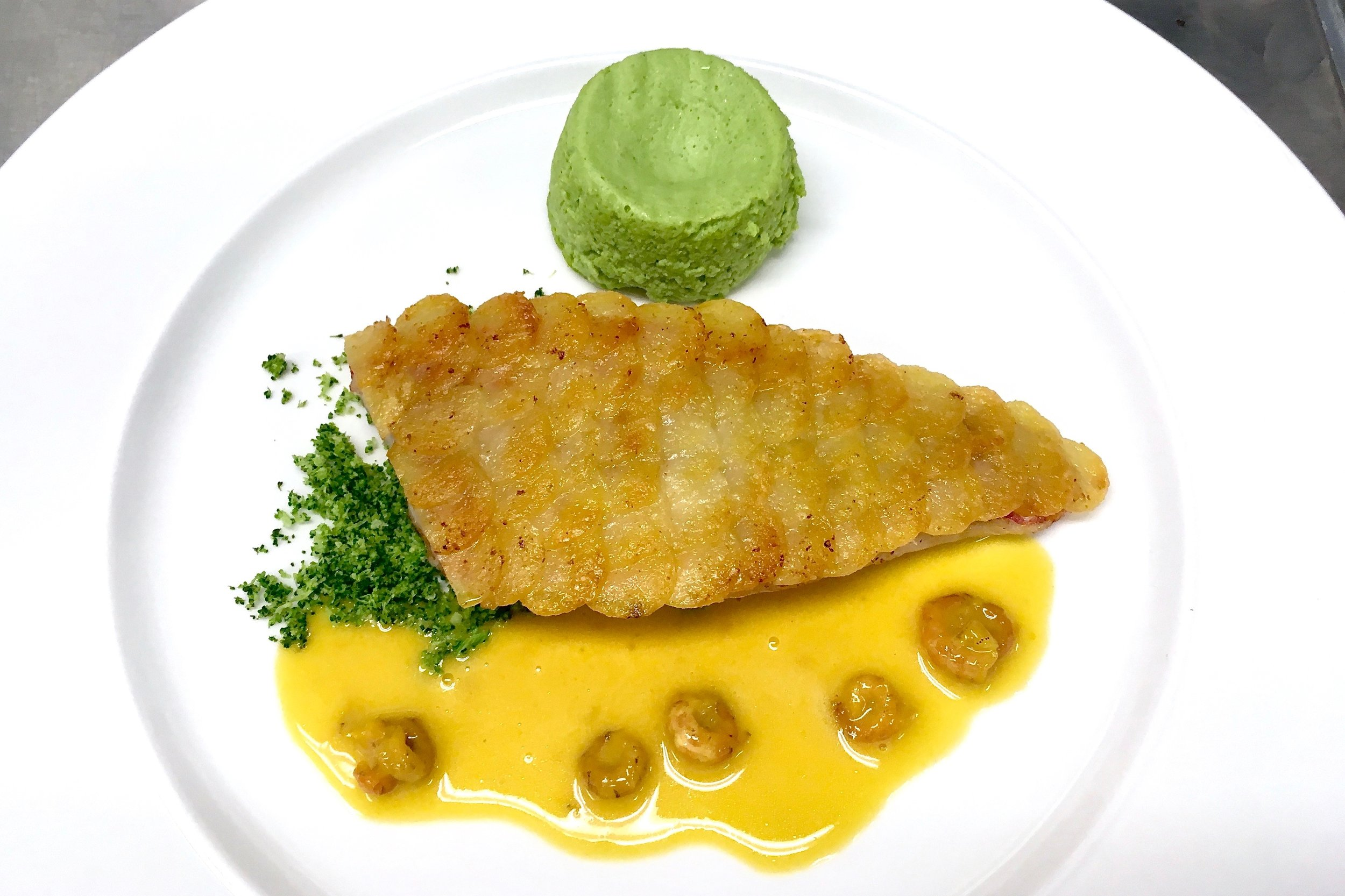 Red mullet with crispy potato scales in a saffron and vermouth sauce with a broccoli flan