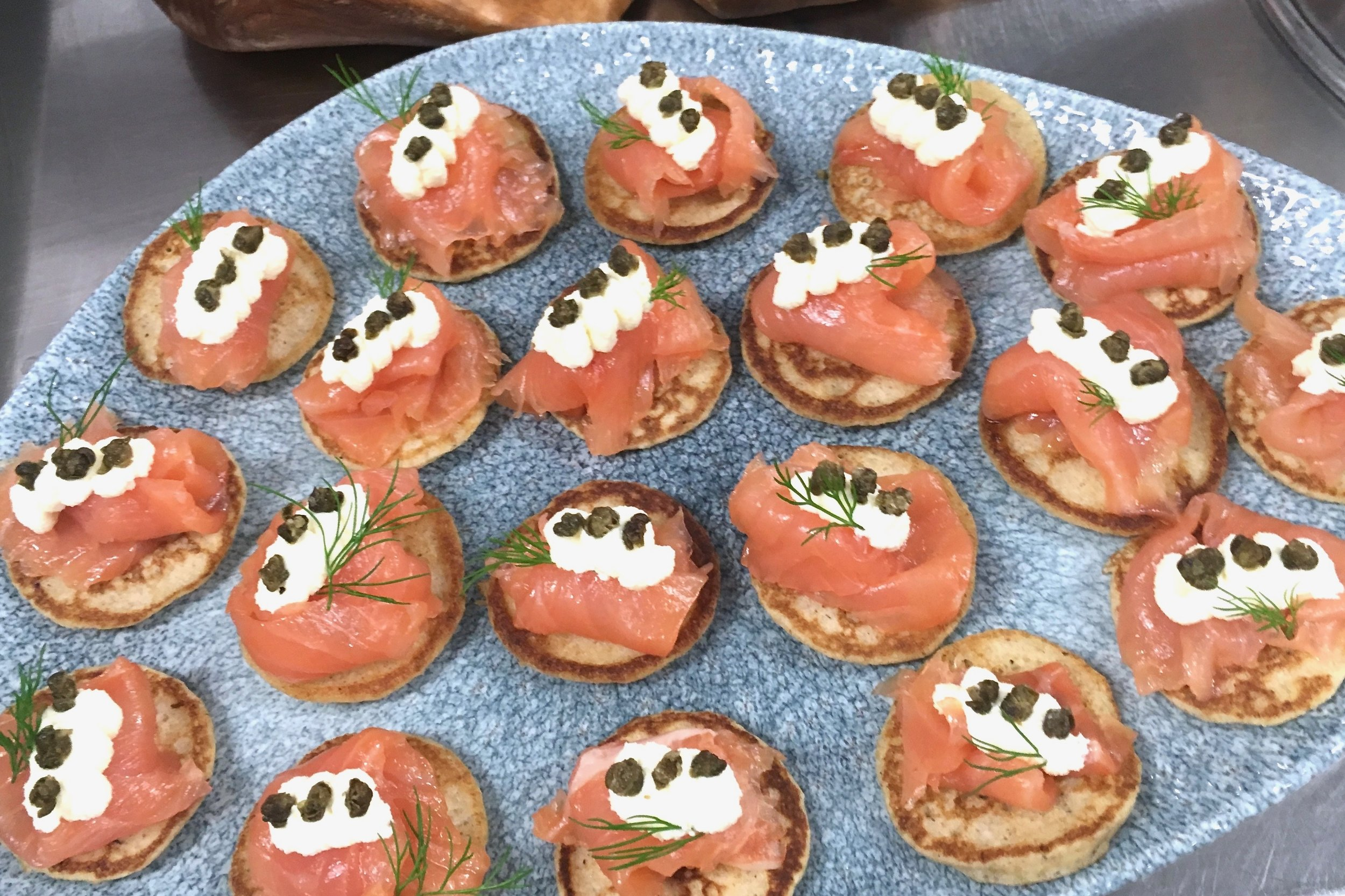 Smoked salmon on blinis with horseradish cream, crunchy capers and dill