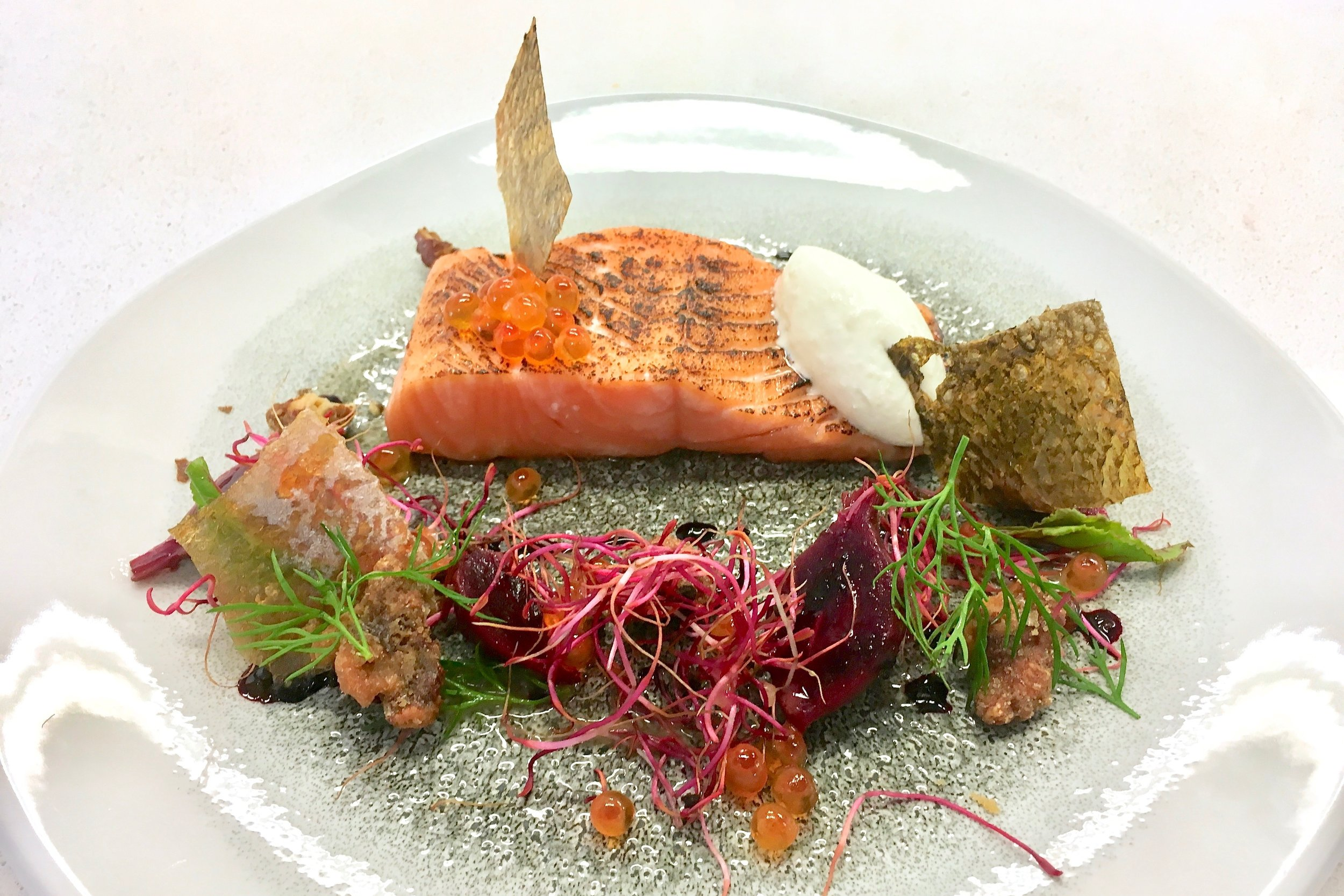 Charred salmon with crispy skin, roast baby beetroots, a beetroot syrup, horseradish cream and caramelised walnuts