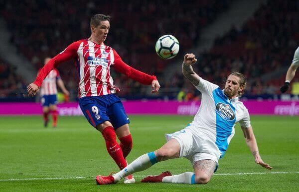 Atletico Madrid striker Fernando Torries dribbles against Malaga in La Liga competition