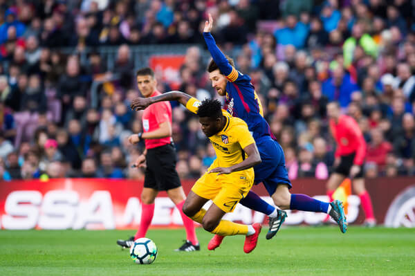 Lionel Messi of FC Barcelona fouls Thomas Partey of Atletico de Madrid during the La Liga match between Barcelona and Atletico Madrid at Camp Nou on March 4, 2018 in Barcelona, Spain.  (March 3, 2018 - Source: Alex Caparros/Getty Images Europe)