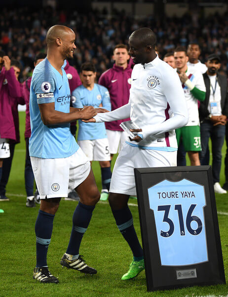 Vincent Kompany of Manchester City embraces Yaya Toure of Manchester City as he is presented with a shirt in a frame during the Premier League match between Manchester City and Brighton and Hove Albion at Etihad Stadium on May 9, 2018 in Manchester, England.  (May 8, 2018 - Source: Gareth Copley/Getty Images Europe)