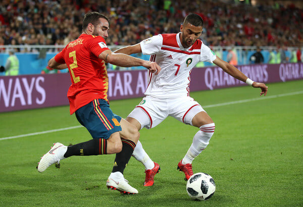 Dani Carvajal of Spain crosses the ball under pressure from Hakim Ziyach of Morocco during the 2018 FIFA World Cup Russia group B match between Spain and Morocco at Kaliningrad Stadium on June 25, 2018 in Kaliningrad, Russia.  (June 24, 2018 - Source: Julian Finney/Getty Images Europe)