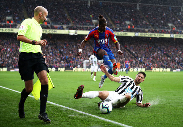 Wilfried Zaha of Crystal Palace jumps clear of a challenge from Federico Fernandez of Newcastle United during the Premier League match between Crystal Palace and Newcastle United at Selhurst Park on September 22, 2018 in London, United Kingdom.  (Sept. 21, 2018 - Source: Julian Finney/Getty Images Europe