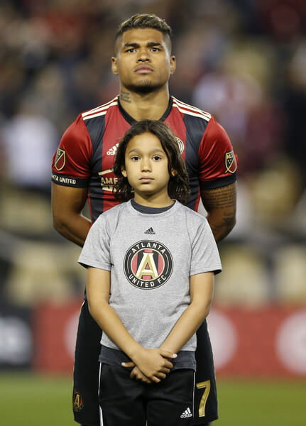 Forward Josef Martinez #7 of Atlanta United stands with a young fan for the national anthem before the game against the New York Red Bulls at Bobby Dodd Stadium on March 5, 2017 in Atlanta, Georgia.  (March 4, 2017 - Source: Mike Zarrilli/Getty Images North America)