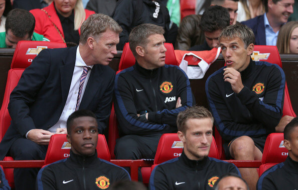 Manchester United manager David Moyes talks with Steve Round and Phil Neville during the Rio Ferdinand Testimonial Match between Manchester United and Sevilla at Old Trafford on August 9, 2013 in Manchester, England.  (Aug. 8, 2013 - Source: Clive Brunskill/Getty Images Europe)