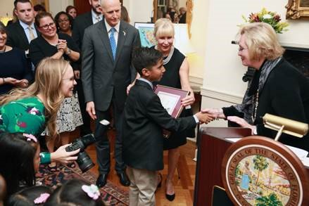 On behalf of Florida Prepaid, Cynthia O'Connell awards scholarships to Hispanic Heritage Month Essay Contest winners.