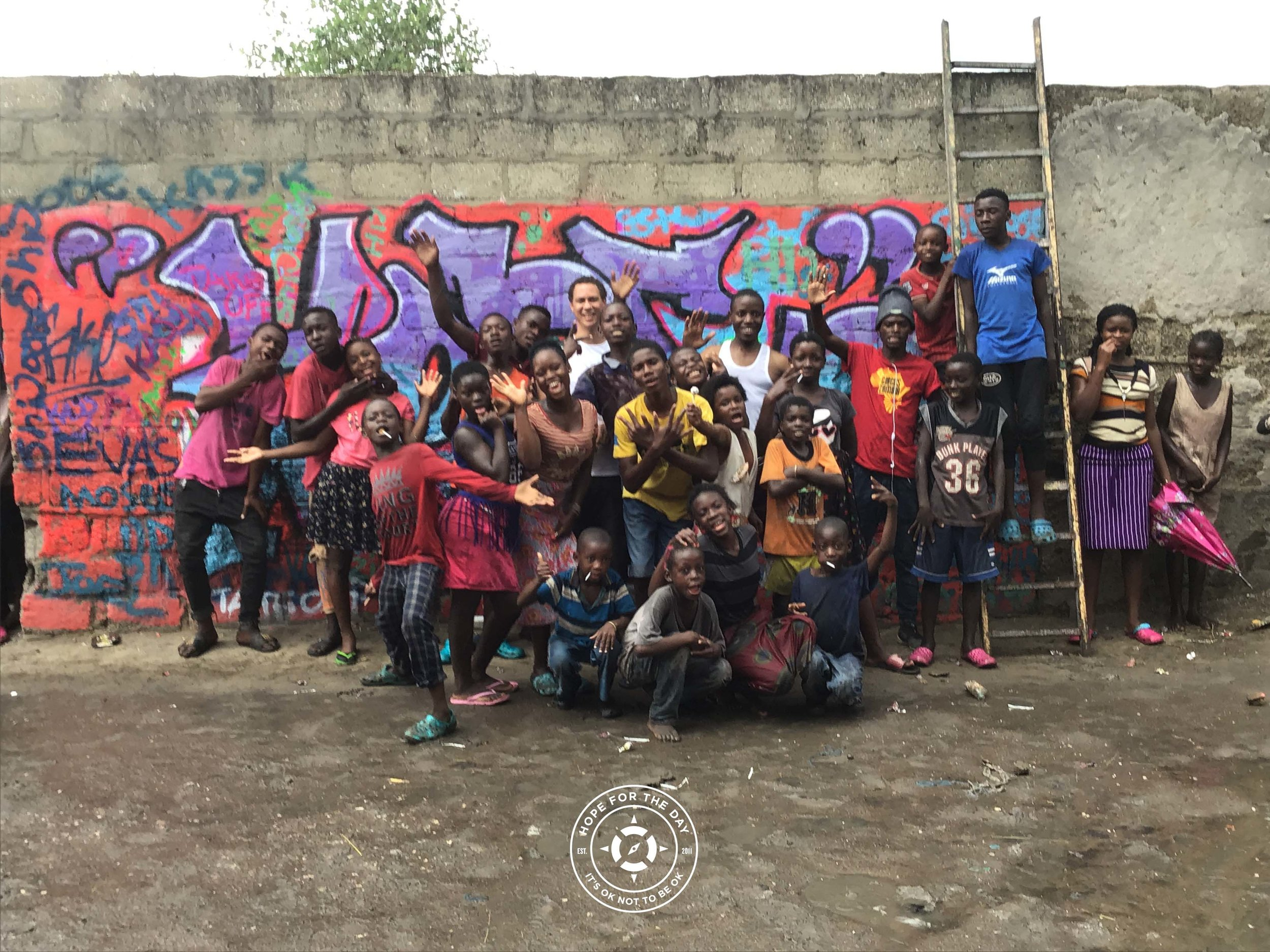 """Group photo in front of the newly completed """"Hope"""" mural with Zambian artist Dwain Whitaker. Credit: Nancy Bartosz"""
