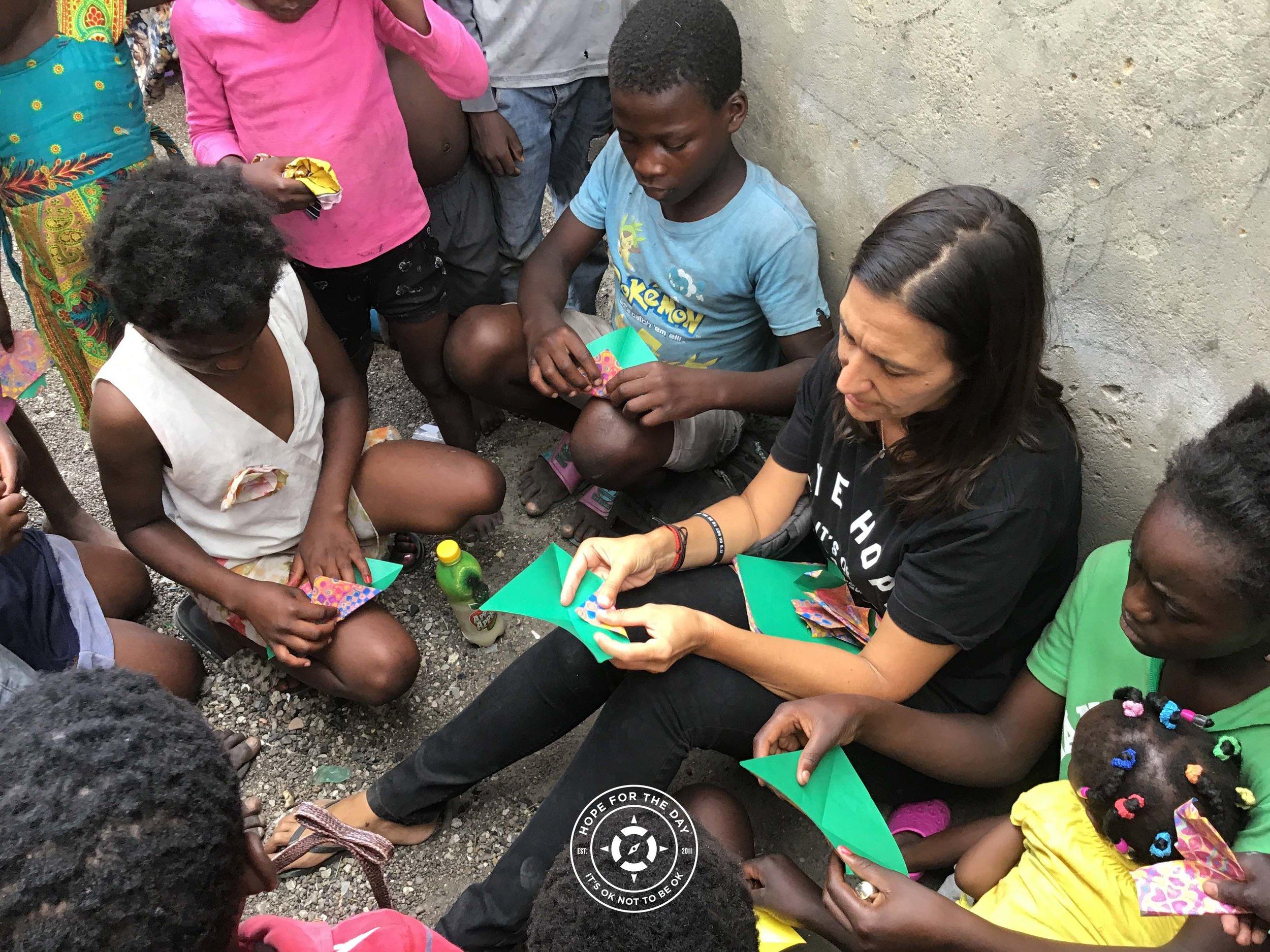 Taking a break from the spray paint to teach origami in Uganda. Credit: Nancy Bartosz