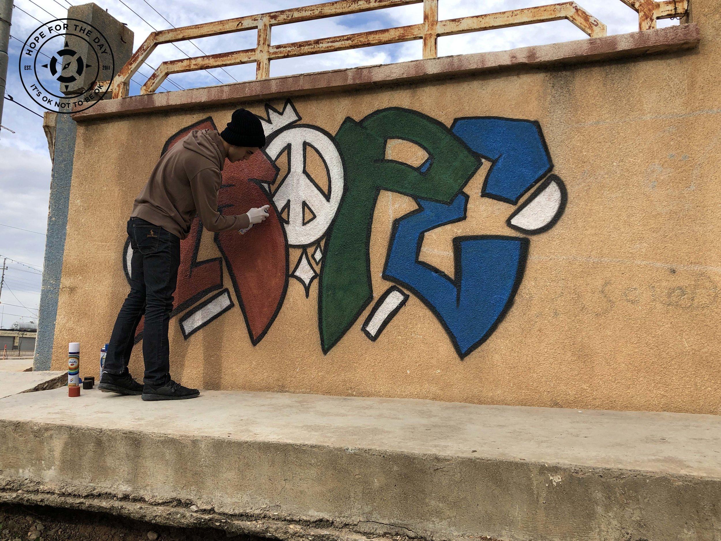 Artist Mira Graff creating a mural in Kurdistan. Photo: Nancy Bartosz