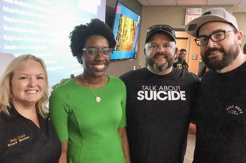 Joel Frieders (wearing the Talk About Suicide T-shirt) and HFTD Education Director, Mike Vinopal speak with Rep. Lauren Underwood at the Kendall County Health Department in Yorkville, IL regarding suicide prevention and mental health resource availability.