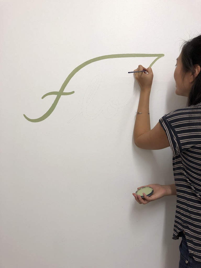 Lizane Tan  painting logo on Flo Meditation + Wellness wall