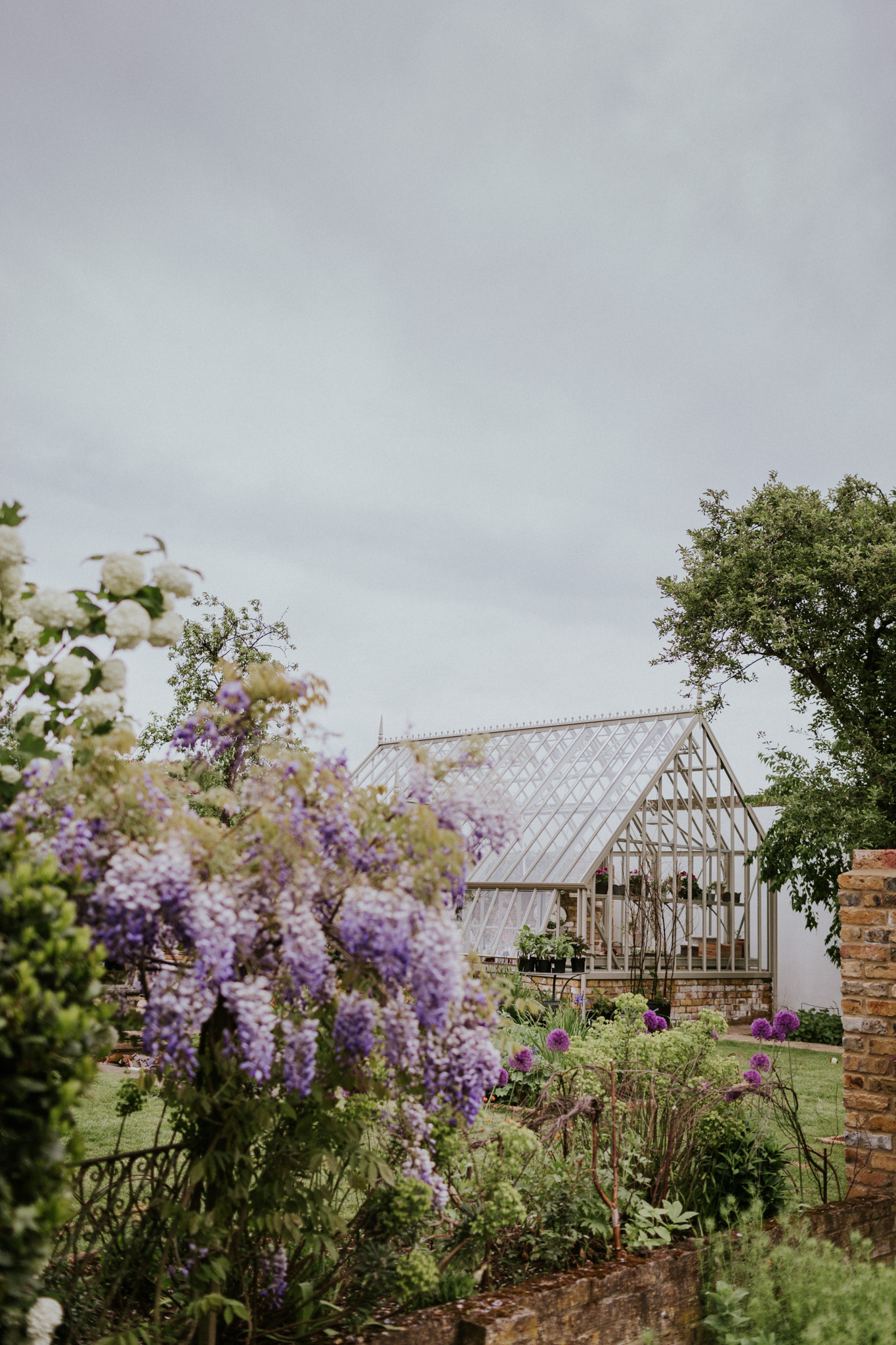 A dreamlike glasshouse in a Secret Garden provides the perfect setting for an intimate wedding party surrounded by lush foliage.