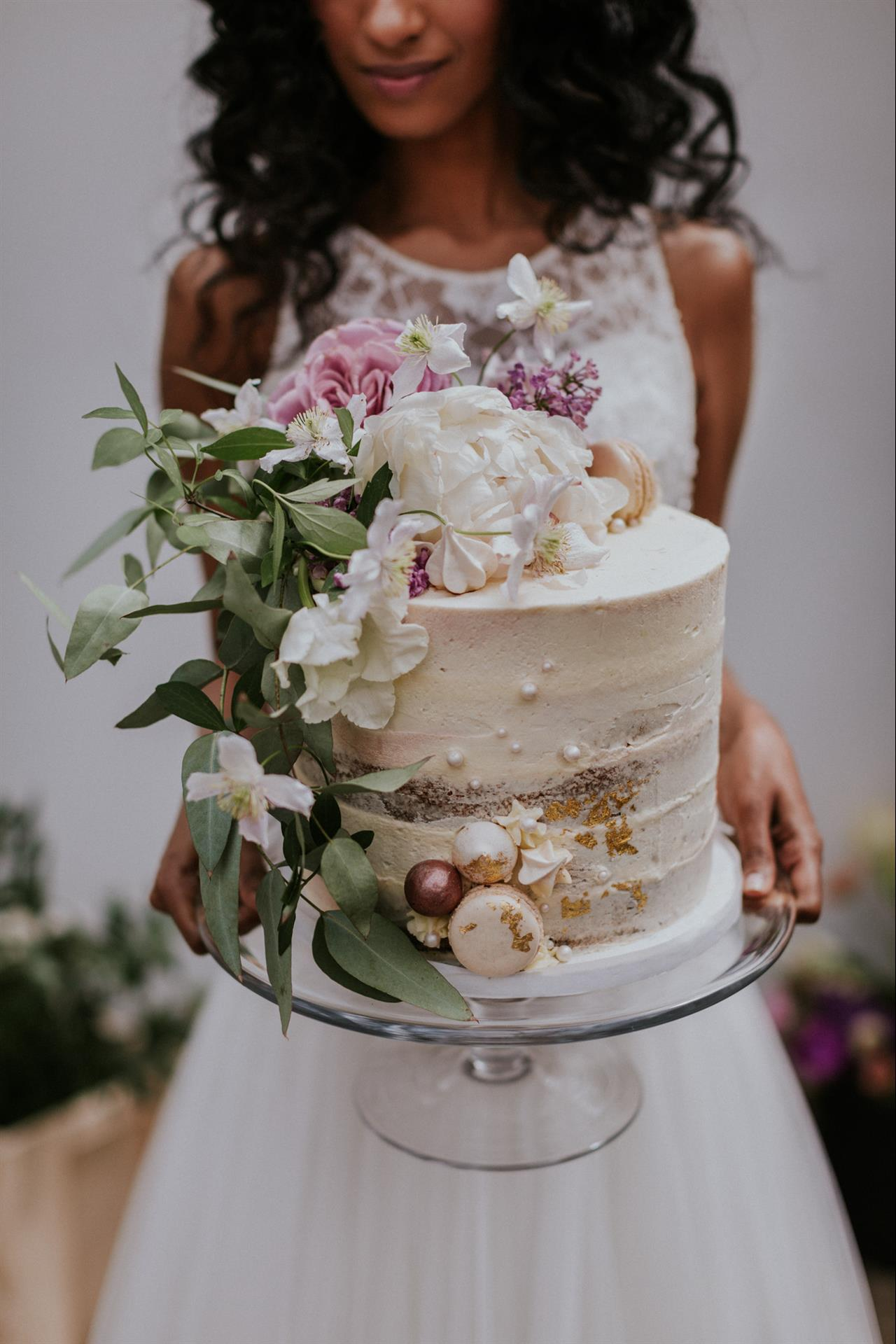 A stunning buttercream wedding cake brimming with English florals and luxurious details.