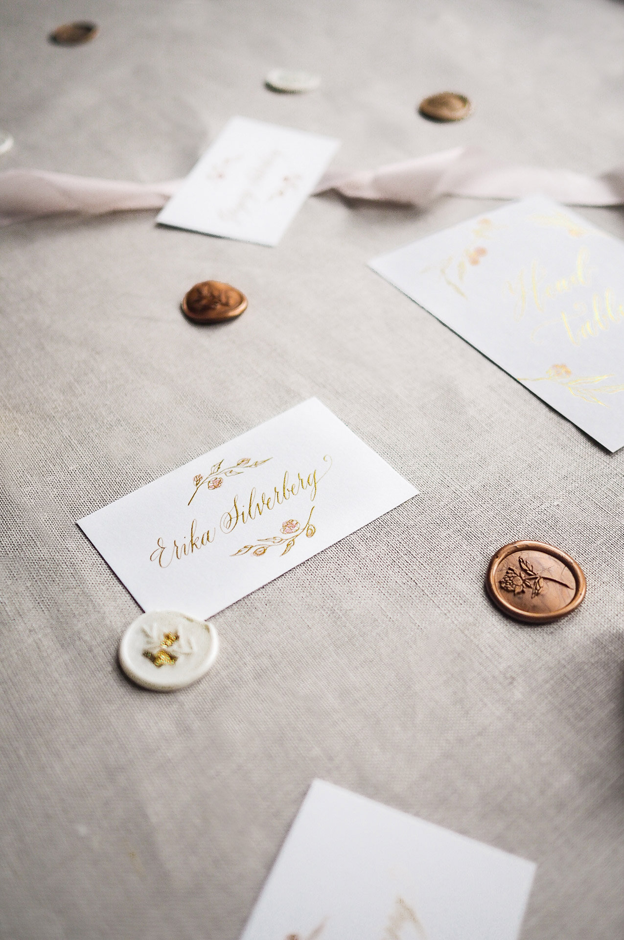 Calligraphy wedding place cards with hand painted floral details.