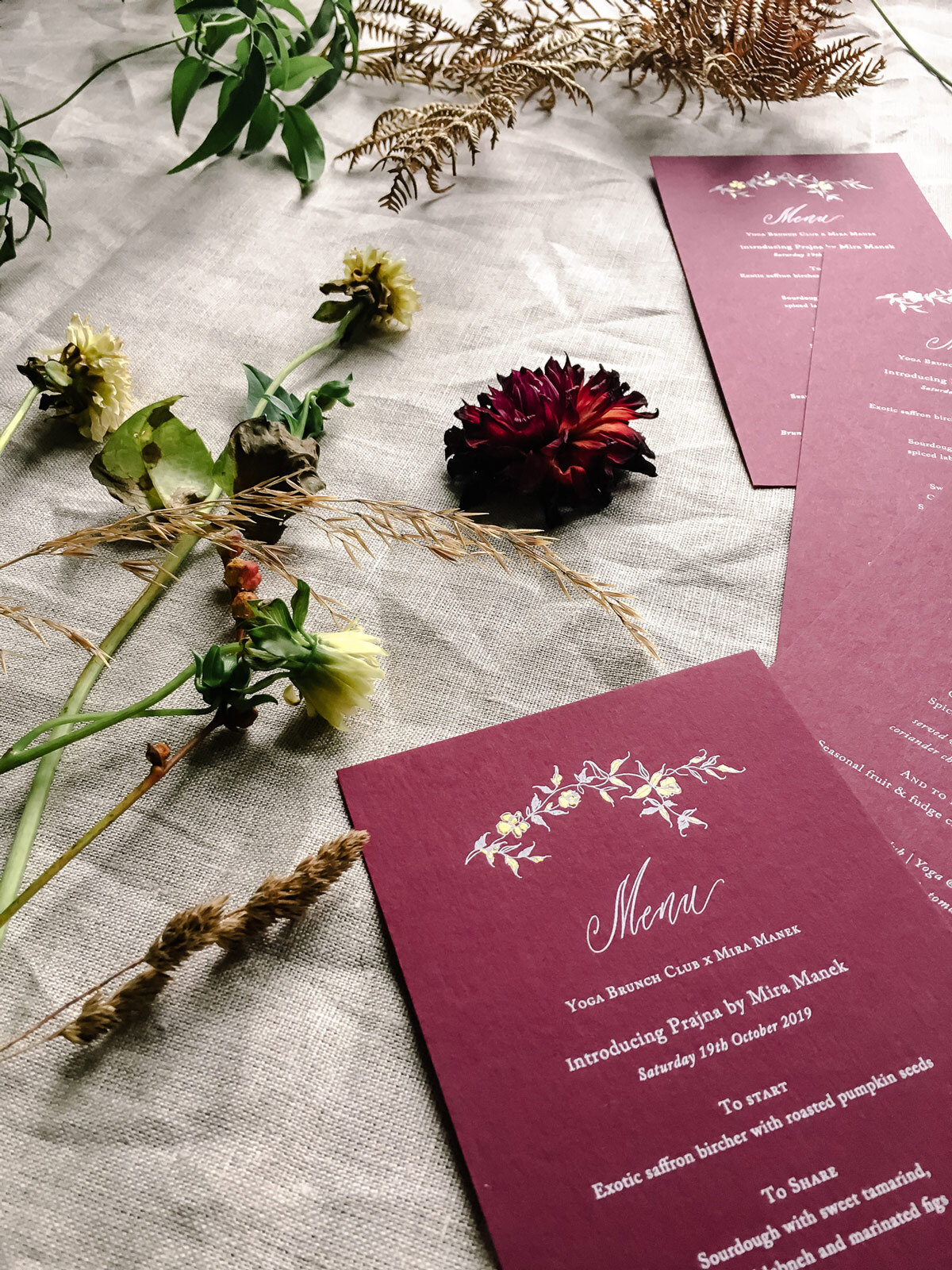Bespoke burgundy menus featuring a floral illustration with touches of hand painted gold.