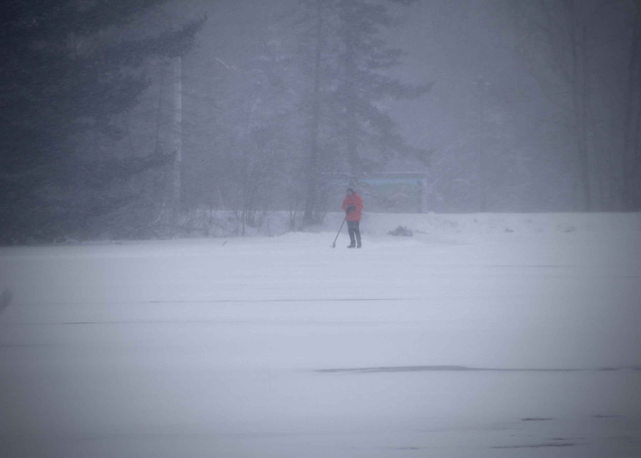 - A lone ice skater with a snow shovel was on the frozen reservoir - clearing snow from the ice for skating.