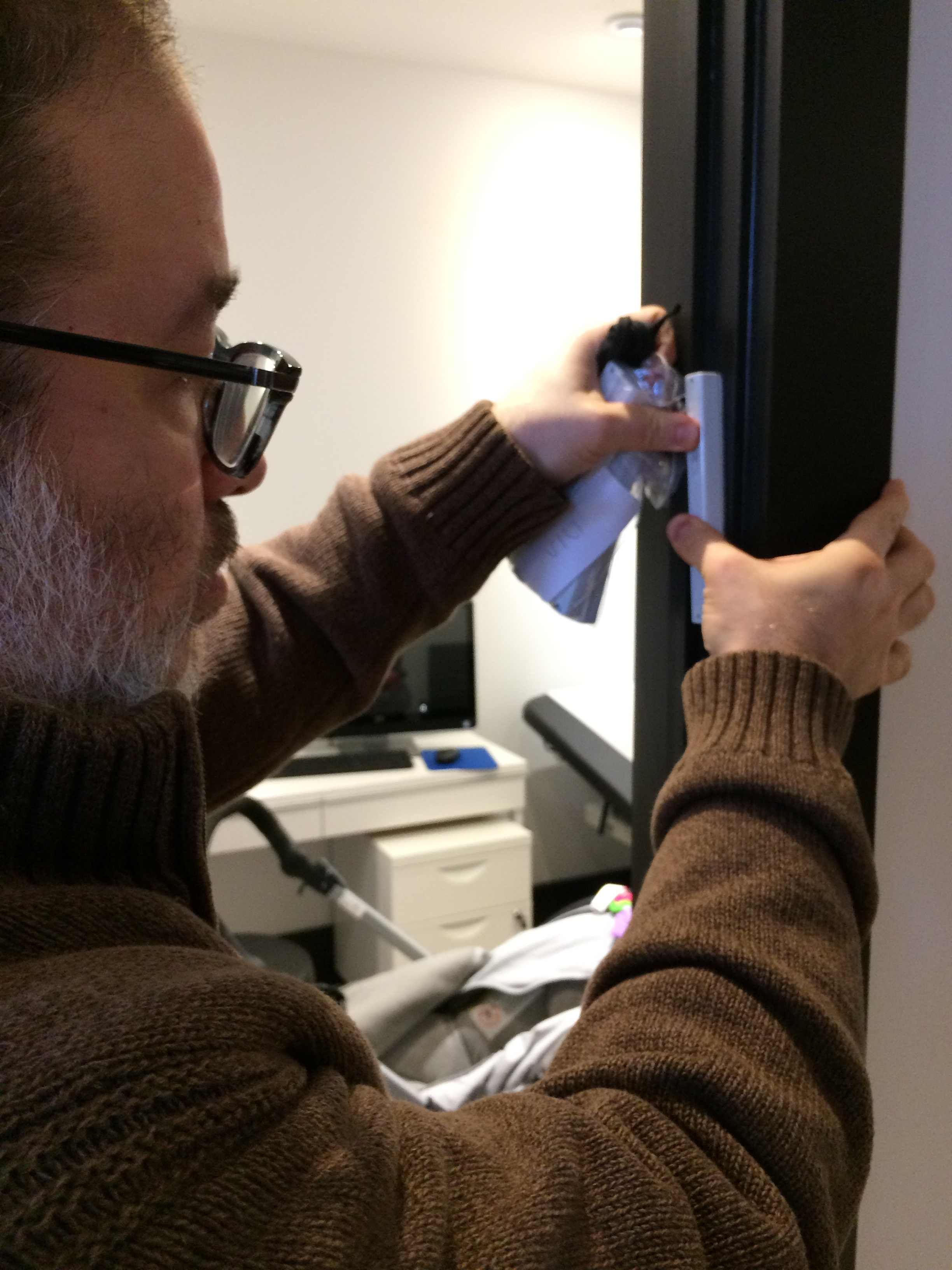 Tomer Meldung, RM Rivky Meldung's partner, affixes a mezuzah to one of our clinic doorways during Uptown Midwives Open House.