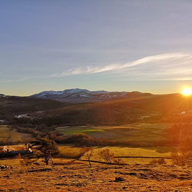 The beautiful golden glow of a winter sunset from just behind the cottage. Lochnagar mountain in the distance with a dusting of snow.