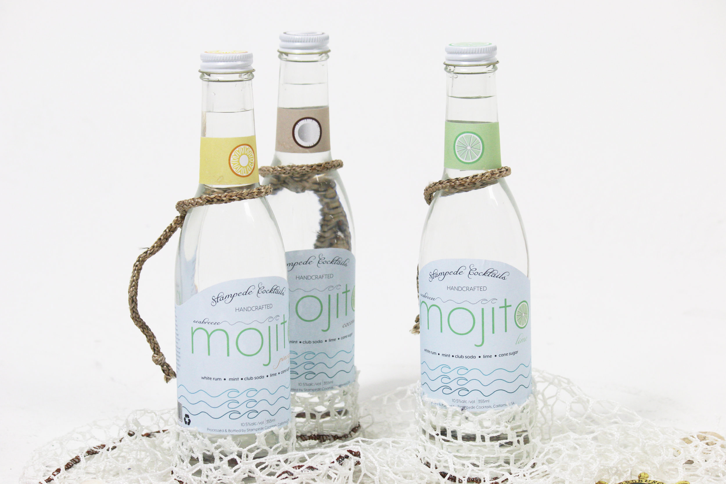 stampede cocktails - Goal of this project was to design a food packaging concept. Stampede Cocktails is a handcrafted drink for people looking to have a bubbly, lime mojito at the beach. The Seabreeze Mojito collection consists of the flavors; Pineapple, Lime, and Coconut. The fishnet attached to the bottom comes from the yacht Stampede, which has sailed all over the world.