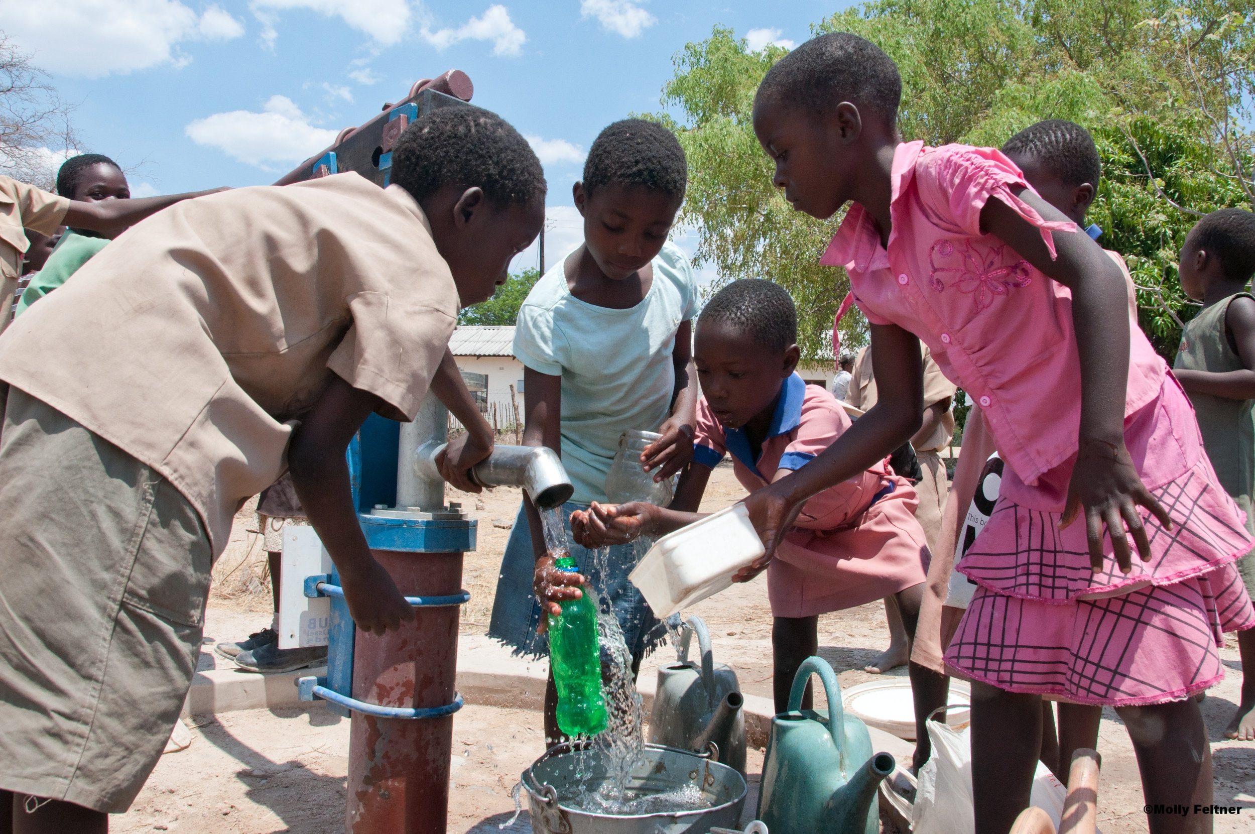 Water is life and we give it. Kids enjoying the rare, at least before in their community, and precious water from a borehole drilled by PDC.