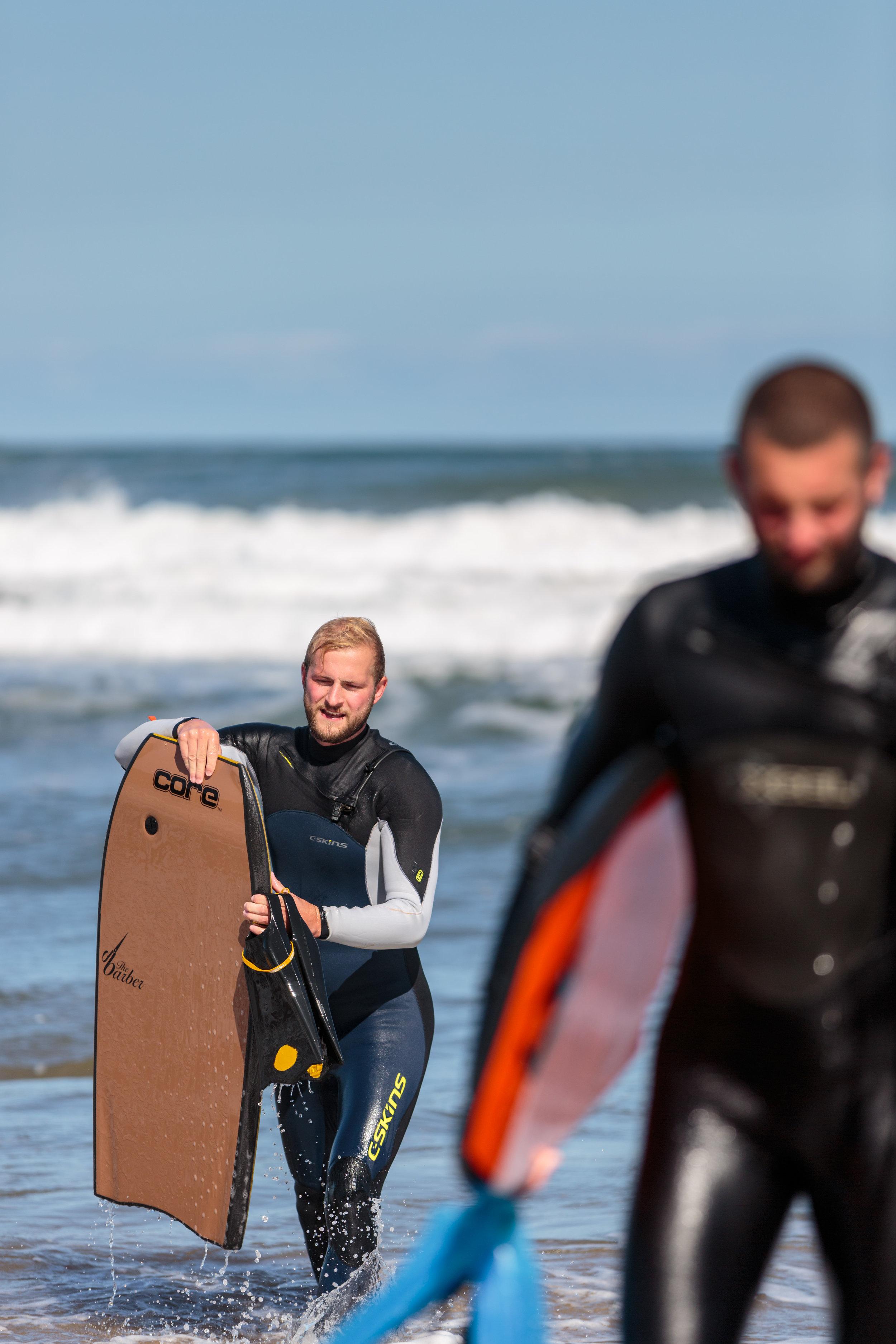 Bodyboarders exiting the ocean