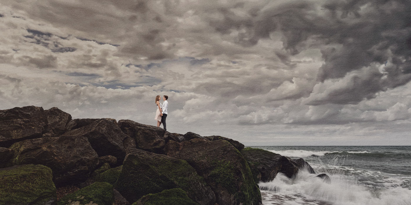 Engaged couple standing on rocks