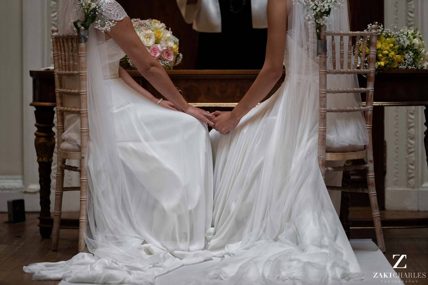 Brides holding hands during ceremony at Hedsor House photo