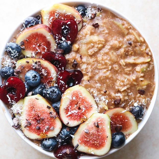 Carob, cinnamon, and zucchini oatmeal topped with blueberries, cherries, and fig.