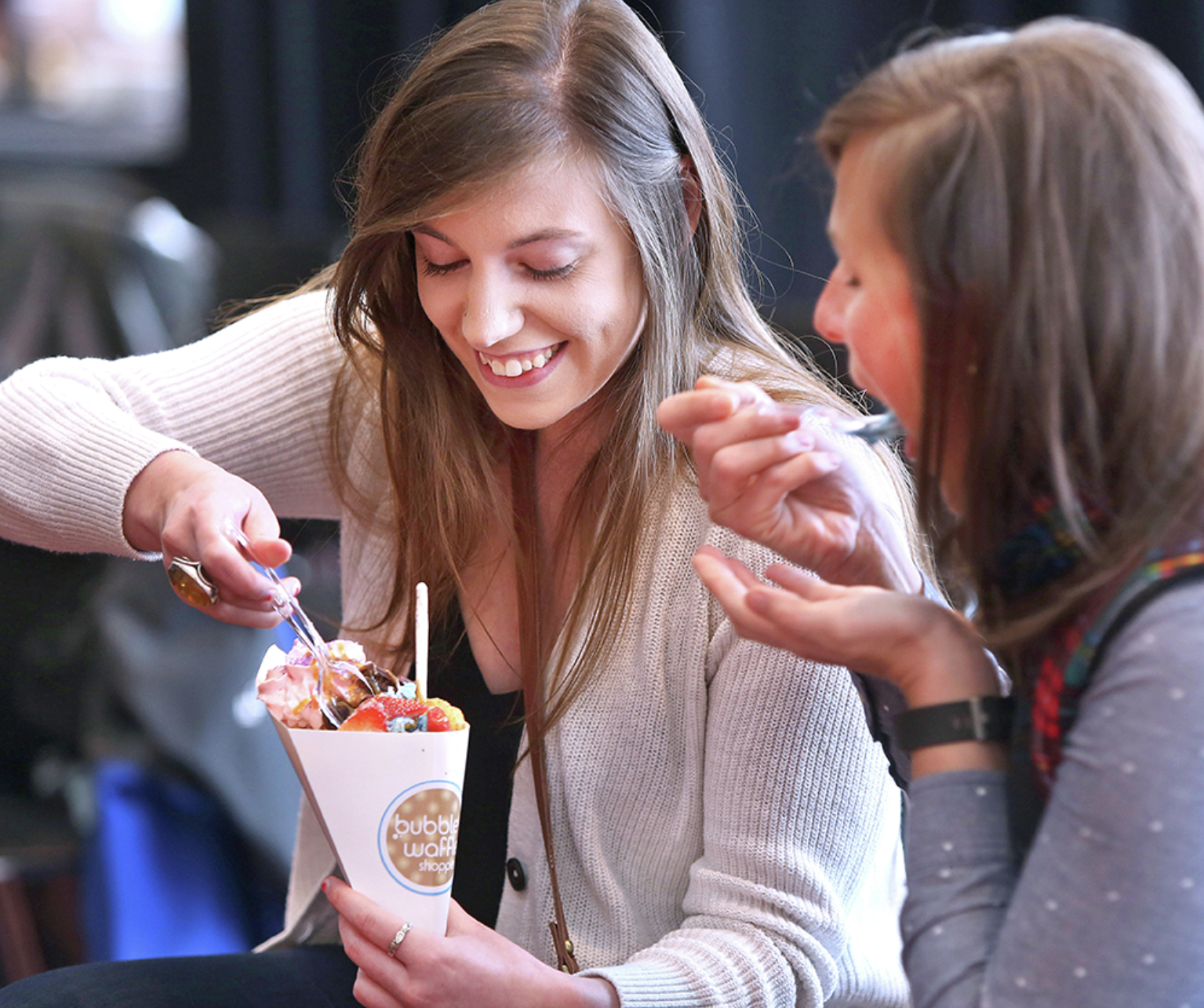 """So-o-o good,"" said Megan Gosch (left) as she reaches for a spoonful of her bubble waffle at the pre-Super Bowl menu tasting for media Wednesday at TCF Stadium in Minneapolis. ""It's so beautiful to look at,"" said her colleague Morgan Halaska. Bob King / rking@duluthnews.com"