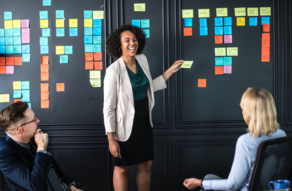 Young black woman stands in front of wall of post its while leading a design thinking workshop with her colleagues.jpg