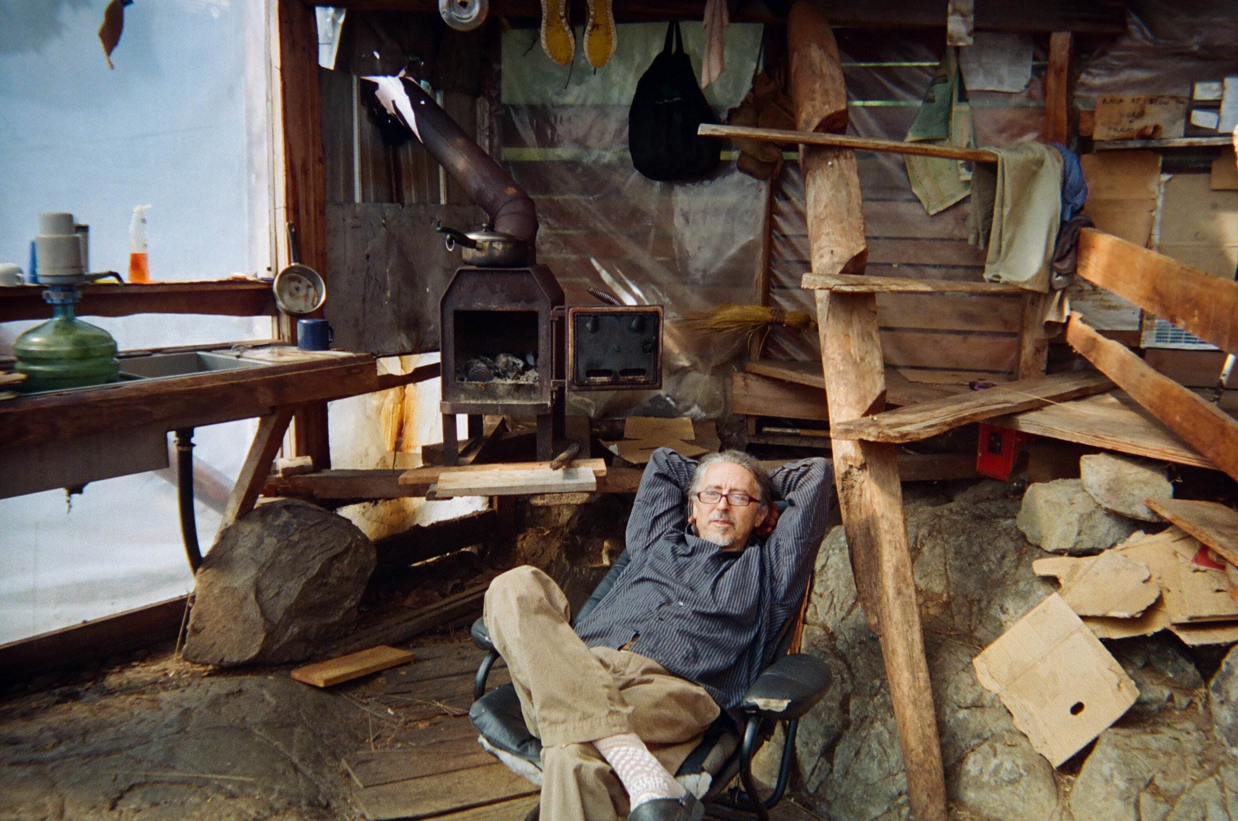 Gerry reclines by the yurt's hearth, enjoying his pace of life.