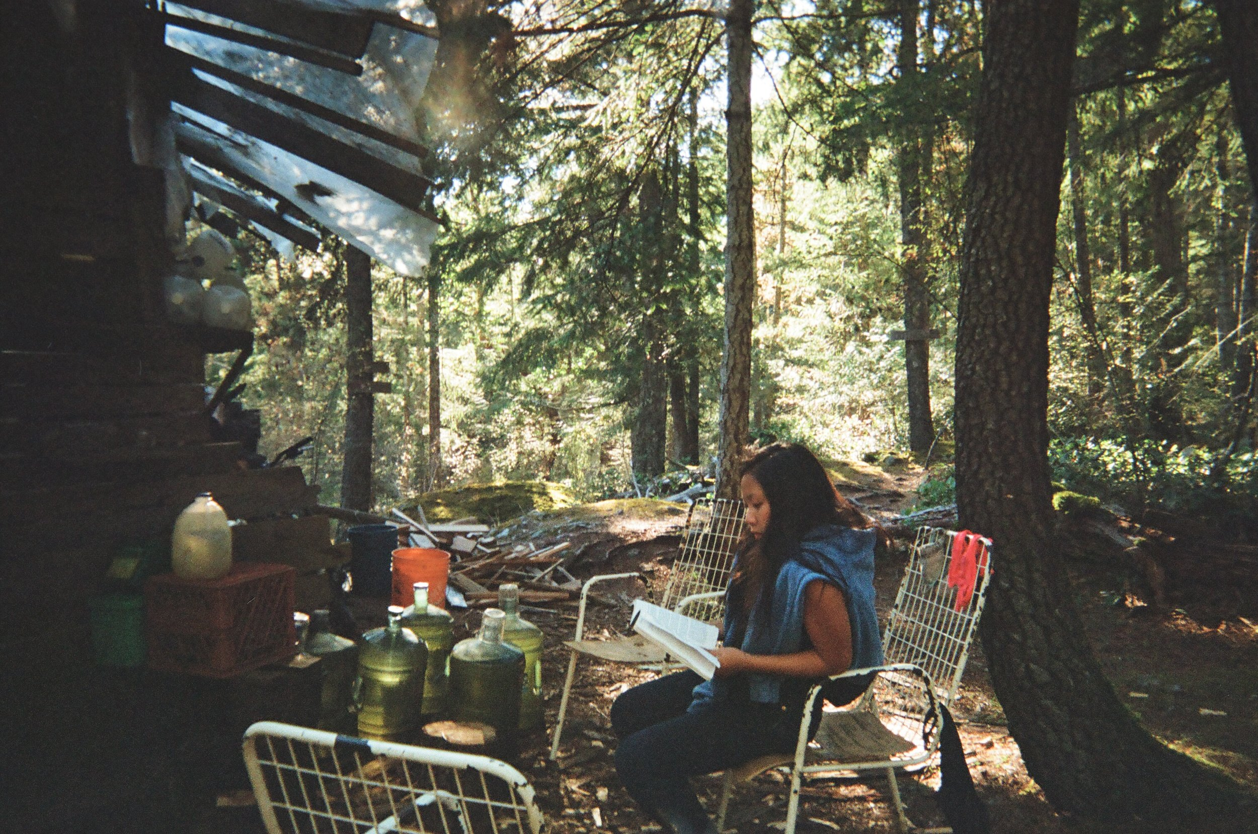 Cherry reading at the yurt, by jugs of collected rainwater, snapped with my Konica on 35mm film.