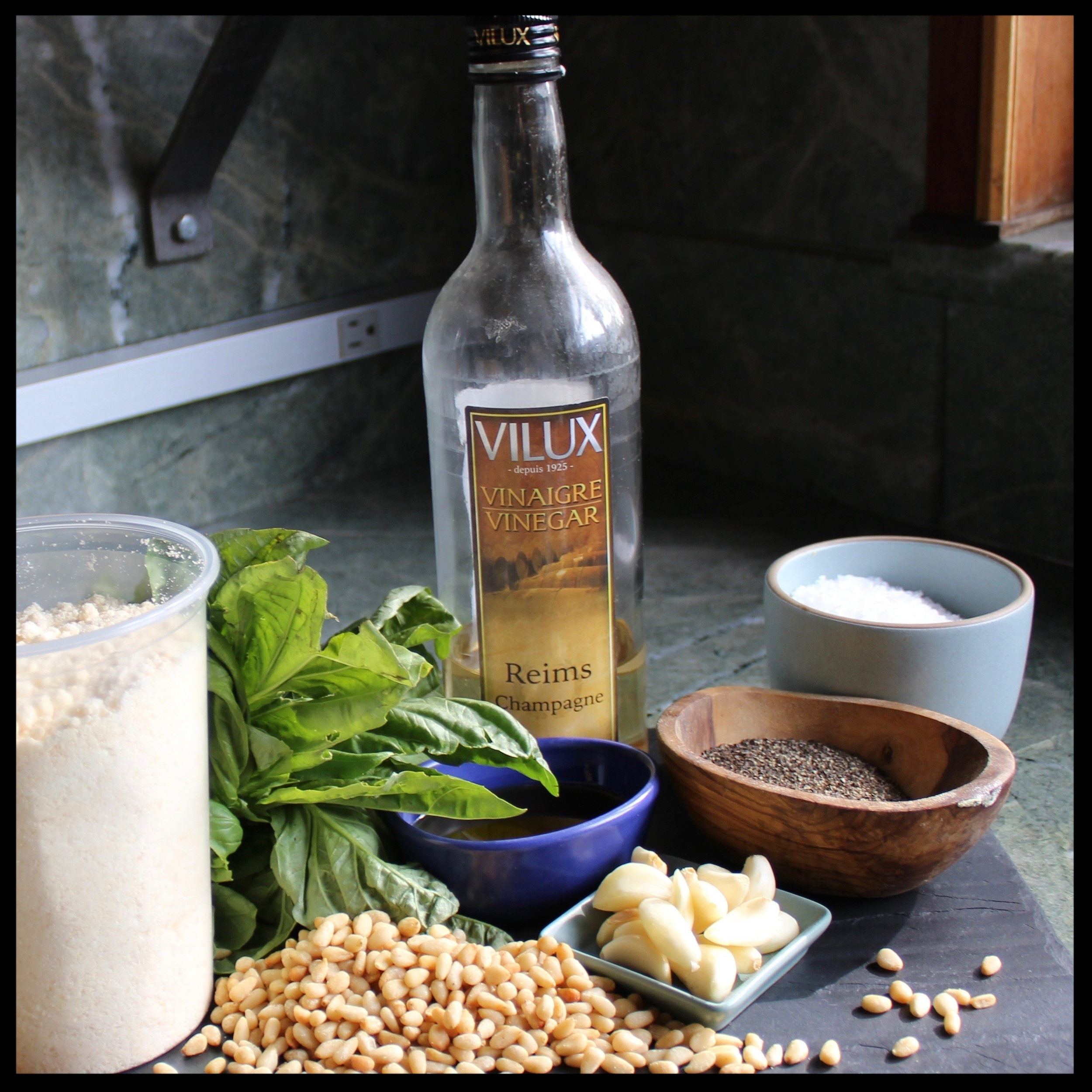 WHAT YOU NEED:   - 6 cloves garlic  - 1 bunch (approx 8oz) fresh basil  - 1/2 cup toasted pine nuts (pignoli)  - 1 cup grated parmesan or pecorino romano (I used mix of both - parmesan is nutty/buttery, and romano salty/sharp)  - 1/2 cup extra virgin olive oil  - 1/4 cup champagne or white wine vinegar  - salt and pepper